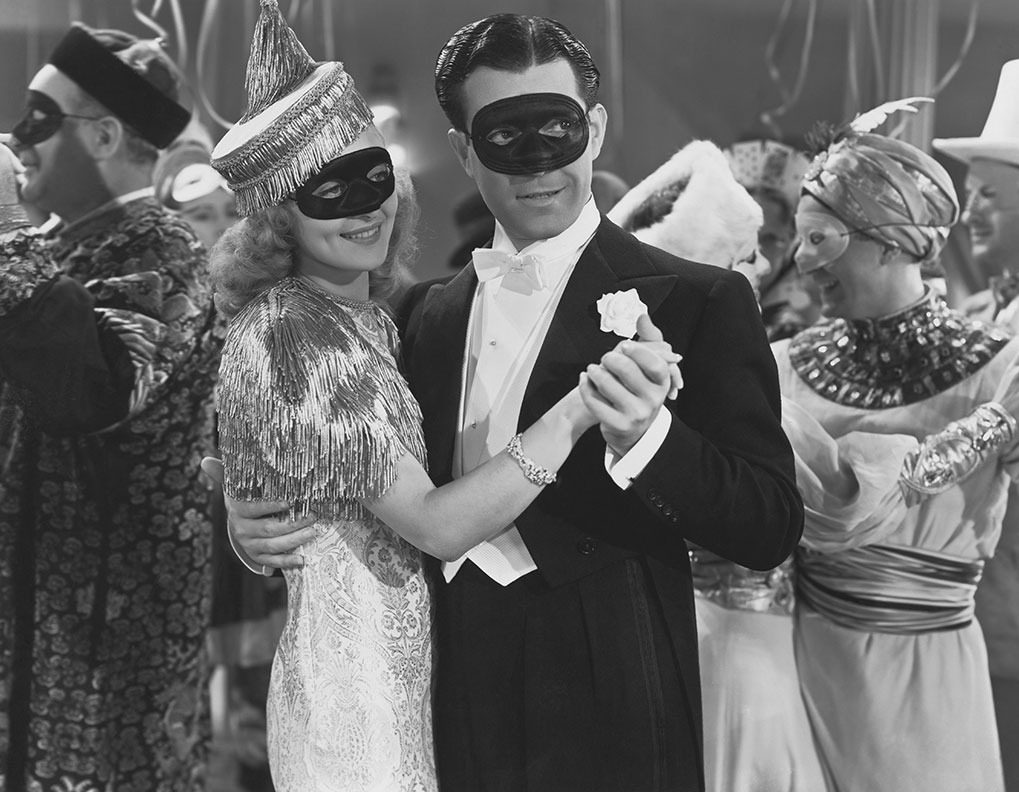 couple posing at a masquerade ball